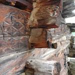 Details am Stall Leng Flüe, die auf ein altes Wohnhaus weisen: Die Hälfte einer Fensteröffnung in der talseitigen Wand und Rosetten in Kerbschnitztechnik auf der einstigen Stubenbinde, heute die Aussenwand des Stalls.