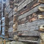 Rückseitig stehen die Kantholzenden der Trennwände vor und zeigen, in wie viele Abteile der breite Bau unterteilt ist.