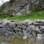 Wohin mit den Steinen, die das Gras erdrücken? Die Flur Wigguhüüs zeigt zwei traditionelle Lösungen: Steine dienen zum Mauerbau entlang der Wege; zusammengeklaubte Steine werden zu Haufen geschichtet.