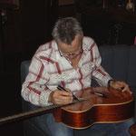エアーズのギターにサインを書くトミー(2007年来日時)