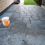 geklopfte Granit-Naturplatten auf frischen Mörtel. Fundation aus Sickerbeton