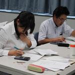 関数電卓をたたきながら演習問題に取り組む県測協の会員