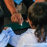 Die Kinder lernen wie sie auf ihre Tafel zu schreiben haben