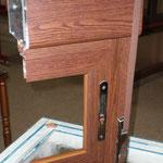 Detalle corte en sección de ventana aluminio corredera imitación madera, persiana compacta integrada, herraje oro envejecido en cierre embutido y recogedor de cinta.