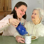 Visiting Angels caregiver pouring some tea for her care recipient