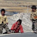 Trois petits bambins bien souriant qui jouaient sur le bord de la route