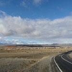 Un village dans la steppe avec au loin les sommets enneiges