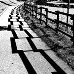 Schattengeometrie auf dem Fahrradweg s/w voll kontrastet