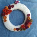 ghirlanda rivestita in lana, decorata con fiori in lana e panno, perle di legno. Diametro cm 15 circa. Venduta