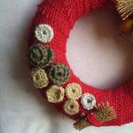 ghirlanda in juta color rosso corallo, fiori in lana e panno, perle di legno. Diametro cm 15 circa. Anima in polistirolo.Venduta