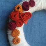 ghirlanda rivestita in lana, decorata con fiori in lana e panno, perle di legno. Diametro cm 15 circa.