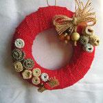 ghirlanda in juta color rosso corallo, fiori in lana e panno, perle di legno. Diametro cm 15 circa. Anima in polistirolo. Venduta