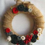 ghirlanda in juta grezza, fiori in lana e panno, perle di legno. Diametro cm 15 circa. Anima in polistirolo. Venduta