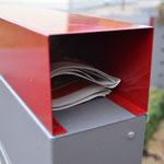 Zeitungsrolle oben auf Briefkastenstele montiert