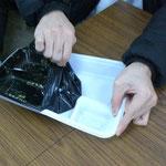 はがす弁当: 京大生協の各ショップでは、いわゆる「はがす弁当」とよばれる弁当が販売されています。この写真は、食べ終わった後にフィルムをはがしているところです。はがした後のトレーを再利用することで、ゴミの量をかなり削減することが出来ます。