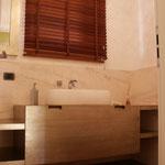 mobile da bagno sospeso in massello di larice spazzolato rivestito in foglia argento anticata a mano, con dettagli di tagli a 45° e maniglia ricavata nello spessore. Lavabo in tecnomarmo