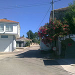 Das Nachbarhaus beobachtet die Gegend. Rechter Hand liegt die Bushaltestelle, dahinter ein frei wachsender Oleanderstrauch.