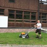 Rasenmähen bei der Schule, mit neuem E-Rasenmäher