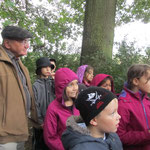 Horst Leismann und die Kinderschar lauschen fasziniert