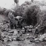 Deutsche Fallschirmjäger untersuchen Kriegsmaterial in einem Hohlweg