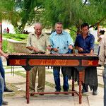 Drei Männer spielen die Marimba.