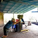 """Zuesrt kommt der Zuckerrohrsaft. Zwei Touristen bedienen die Zuckerrohrpresse. Normalerweise laufen hier """"echte"""" Ochsen."""