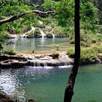 Ein Rückblick auf die Terassen, darunter rauscht der Fluss durch eine Höhle.