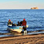 Eine ganze Reihe von Fischern fahren abends mit kleinien Booten los.