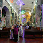 Der Priester begrüßt vor der Messe die eintretenden Kirchgänger.