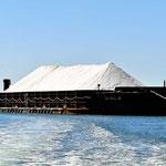 Eine der riesigen Salzschuten, die das frisach gewonnene Salz aus der (flachen) Bucht zu einenm Tiefwasserhafen bringt.