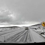 """Schnee liegt auf der Straße - und prompt gibt es einen Unfall, ein dickes Auto rutscht von der Straße und """"kentert"""" im Straßengraben."""