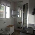 Badezimmer mit Doppelwaschbecken und Handtuchheizlüfter