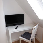 Konsolentisch und LED-TV im Dachgeschoss-Schlafzimmer