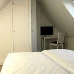 Schlafzimmer im Dachgeschoss, hier Einbauschrank und LED-TV