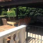 obere, überdachte Terrasse mit Loungemöbeln und Essgruppe sowie Außenkamin