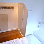Blick vom Bett in den kleinen Schlafraum mit hübschen Einbauten im friesischen Landhausstil