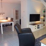 Salon avec Flat-TV, place à manger, la cuisine est derrière le mur