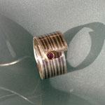 Streifen-MokuMeGane - Seitenabschnitt eines Schichtblocks aus 500er Palladium und 935er Silber weiterverarbeitet zu einem offenen Spiralförmigen Ring, Stein: violetter Safir