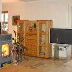 Wohnzimmer mit TV und Kaminofen