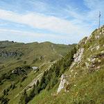 Das Gipfelkreuz auf dem Portlahorn mit dem Steilabfall nach Westen.