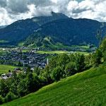 Blick über eine Alpwiese auf Bezau und die Hangspitze