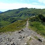 Der Kamm und Wegverlauf noerdlich des Portlakopfs zum Suenserjoch. Links vom Weg der Suenser See.