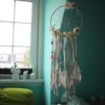 Traumfänger mit Federn - Perlen - Blüten vor einem Fenster aufgehängt.