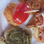 """Pikante Blätterteig-Schnecken, mal im roten, mal im grünen Gewand; in bester Nachbarschaft mit den indischen Linsenbällchen und """"Mett""""-Schnittchen."""