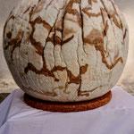 """Lampe """"Sentiers terrestres"""" H : 31 cm et Ø 32 cm environ en laine mérinos, mousseline de soie, soie tussah, toison mérinos, maille cachemire, sur socle en liège, système électrique et lampe LED."""
