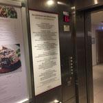 Informationsschild im Lift eines Hotels: von der Rückseite gestaltete Acrylfläche