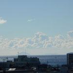△の形の利島 その右の台形の新島の上空にもくもくした雲が湧いています。