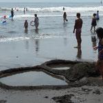 砂のアートの力作を作っている子もいました。熱海は観光のために 全部白砂に入れ替えたそうですが、湯河原は砂鉄を含んだ黒砂です。