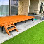 縁側のようなウッドデッキと広い人工芝の庭