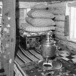 Intérieur d'une isba bashkir, dont l'ameublement n'est fait que de banquettes, de tapis et de coffre, sans oublier le samovar! (PHOTO début 20e)
